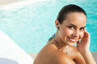 Smiling teenager listening to mp3 player near swimming pool