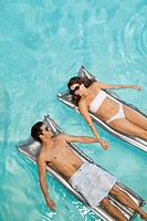 Couple floating in swimming pool sunbathing