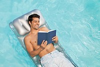 Man floating in swimming pool reading book