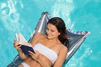 Woman floating in swimming pool reading book