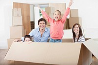 Family playing in moving box in new home