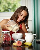 Girl preparing muesli, smiling