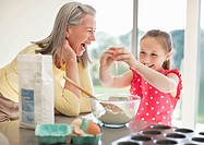 Grandmother and granddaughter baking cupcakes