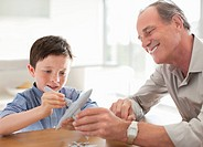Grandfather and grandson assembling airplane model (thumbnail)