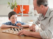 Grandfather and grandson playing checkers together