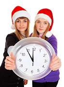 Two girls in New Year´s caps with clock
