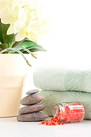 Yellow orchid, massage stones, bath salt and two towels isolated on white background