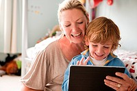 Mother using a digital tablet with her son (thumbnail)