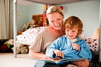 Mother reading a book with her son in his bedroom (thumbnail)