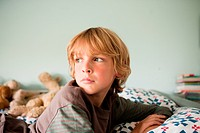 Young boy lying on bed staring into distance