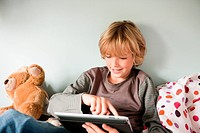 Young boy using a digital tablet while sitting on his bed