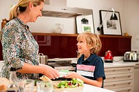 Son helping to carry napkins for mother, in preparation for meal