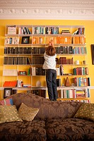 Young boy reaching up to get a book from a bookcase