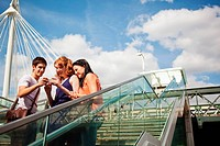 Three people looking at a mobile phone on Hungerford Bridge, London