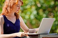 Young woman using a laptop outside (thumbnail)