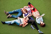 Four people lying down with a laptop, digital tablet and mobile phone