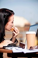 Young woman eating sandwich while using laptop