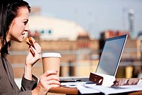 Young woman using a laptop outside while eating a sandwich