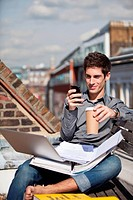 Young man sitting in a roof garden with laptop and mobile phone