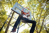 Mid adult man hanging from basketball hoop