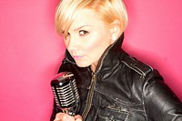 blonde pop star on pink background singing