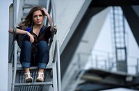 Young, fashionable woman from Afghanistan, living in asylum in the Netherlands, posing near the docks of Rotterdam harbor, sitting on the stairs of a ...