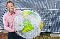 Germany, Munich, Mature man holding globe in solar plant, smiling, portrait