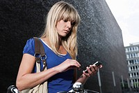 Germany, Cologne, Young woman using cell phone