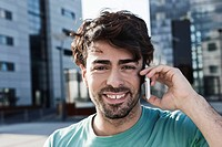 Germany, Cologne, Young man using cell phone, smiling, portrait