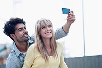 Germany, Cologne, Young couple using cell phone for capturing photo, smiling