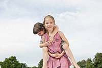 Germany, Bavaria, Girl giving piggy back ride to boy in park, smiling