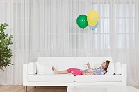 Germany, Munich, Girl lying on couch with balloon