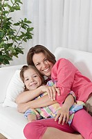 Germany, Munich, Mother and daughter on couch, smiling, portrait