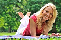 Young smiling woman lying on rug in grass during sunny day park _ outdoors