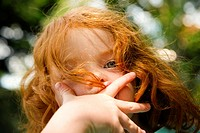Little girl, aged 5, with her hand covering her mouth in a garden  Summer