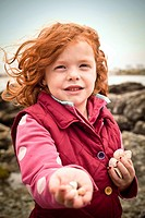 A little girl, aged 5, holding a sea shells on a beach, on a cold day