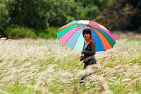 Young lady with colorful umbrella standing in the grass field
