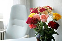 A bouquet of flowers on a table, in the background is a chair.