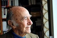 elderly man in front of a bookshelf
