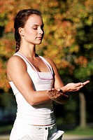 Young woman in an autumnal park practising a medical Qi Gong exercise _ cardiac exercise and small intestine exercise