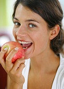 Portrait of young adult woman that into an apple bites and smiles