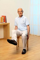 older man is sitting on a chair and doing leg exercises _ senior is doing gymnastics _ lifting lower leg diagonal