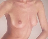 nude _ breast of a young woman , sideways in front of beige background