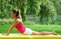 Young blond woman working out on a mat in the park