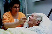 Nurse feeding an elderly woman _ Support of dementia_ill female patients