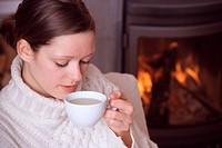 woman sits in front of a chimney and drinks tea