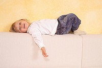 Kid lies on a sofa back and laughs