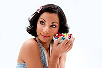 Happy beautiful candy girl with a bowl of colorful bubblegum candy balls next to her cheek, isolated