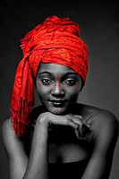 Beautiful traditional African_American woman wearing a authentic tribal red orange head scarf and red dotted makeup, supporting her chin with hand, is...