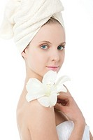 Beauty wrapped in towel holding a flower